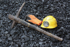 Mining coal. Pickaxe, gloves, mining helmet in the background heap of coal Royalty Free Stock Images