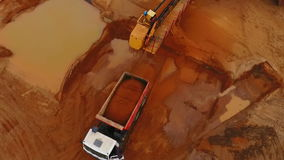 Mining conveyor loading sand in dumper truck. Aerial view of sand mining process stock footage