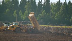 A mining dump truck unloads soil and sand. In a sandy quarry stock footage