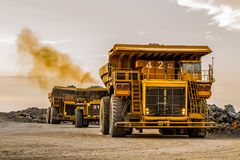 Mining dump trucks transporting Platinum ore for processing. At sunset, Dirty diesel exhaust fumes Royalty Free Stock Photography