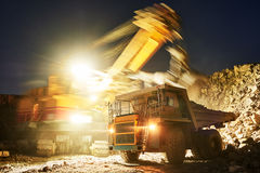 Mining. excavator loading granite or ore into dump truck Stock Photos