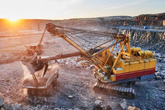 Mining. excavator loading granite or ore into dump truck. Mining industry. Heavy excavator loading granite rock or iron ore into the huge dump truck at opencast Stock Photo