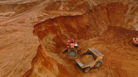 Mining excavator working at sand quarry. Mining industry. Mining excavator working at sand quarry. Aerial view of industrial excavator pouring sand in dumper stock footage