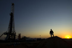 Mining exploration. A mining worker is silhouetted by a exploration rig Stock Photos