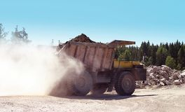 Mining hopper. The mountain lorry rushes on dusty road from career Royalty Free Stock Photo