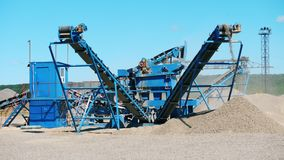 Mining industry equipment. Blue crusher works with breakstones at a quarry.
