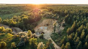 Mining quarry with bulldozer machinery among forest, flying above view or top view. Toned Stock Photo