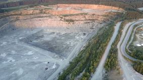 Mining quarry with outdated machines surrounded by roads