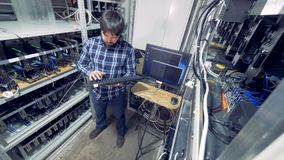 Mining rig with a male specialist in it controlling bitcoin mining process
