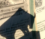 Mining Stock Bull Market. Shadow of a bull over top of antiquated mining stock certificates Royalty Free Stock Photography