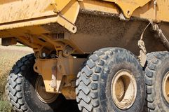Mining Truck. Large yellow mining truck with huge tires at construction site Royalty Free Stock Images