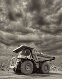 Mining Truck. Heavy mining truck driving through the iron ore opencast with dramatic sky on the background - black and white image Royalty Free Stock Photo