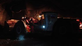 Huge mining truck moves inside dark tunnel in copper pyrite mine