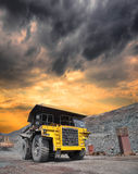 Mining truck on the opencast. Mining truck loaded withiron ore driving along the opencast on stormy sunset Royalty Free Stock Photo