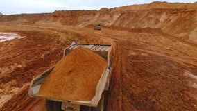 Mining truck transporting sand at sand quarry. Aerial view of mining machinery