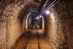 Old Mine Tunnel. Mining tunnel with lights and rails Royalty Free Stock Photography
