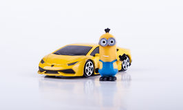 Minion with Yellow Lamborghini. Toy minion smiling and waving next to a yellow toy Lamborghini car isolated on white background. Made in China stock photography