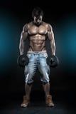 Mięśniowy bodybuilder facet robi ćwiczeniom z dumbbells nad bla Zdjęcia Royalty Free