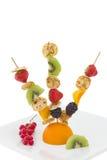 Minipannkaka med klippta frukter på steknålar som isoleras Royaltyfri Fotografi