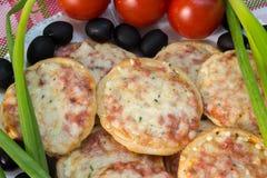 Minipizza mit Tomaten, Frühlingszwiebeln und Oliven Lizenzfreies Stockfoto