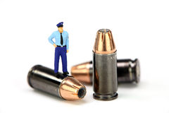 MiniPolizeibeamte, die auf einer Gewehrkugel steht Stockbild