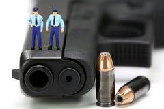 Minipolizisten, die auf einer Gewehr stehen. Stockbilder