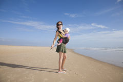 Miniskirt mom with baby in rucksack Stock Photo