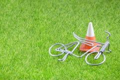 Minispielzeugfahrrad und Verkehrskegel auf einem Gras Lizenzfreies Stockbild