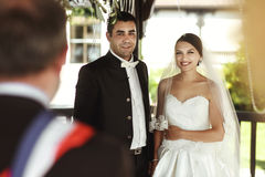 Minister providing wedding ceremony for married couple under arb. Or Royalty Free Stock Photo