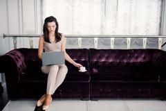 Ministerio del Interior Mujer hermosa joven acertada que se sienta en un sof? en la sala de estar y que usa el ordenador port?til fotos de archivo