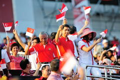 Ministers of State waving flags during NDP 2012 Royalty Free Stock Images
