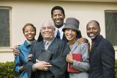 Ministre avec la famille en portrait de jardin d'église Image stock