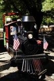 Miniture-Eisenbahn-Zug mit US-Flaggen Stockfotografie
