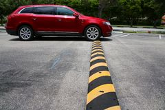 Minivan Driving Over Speed Bump. A red minivan drives up to and just connects with a yellow and black striped speed bump in a parking lot with white diagonal stock image