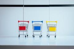 Miniwarenkorb drei oder Supermarktlaufkatze auf Tabelle, Finanzierung und Geldeinkaufskonzept Lizenzfreie Stockfotos