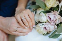 Minnaars die handen met gouden trouwringen houden Bruid en bruidegom Stock Fotografie
