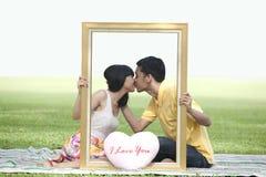 Minnaars die in het park kussen Stock Foto's