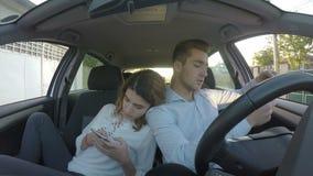 Minnaars die in hun auto zitten rijtjes en op hun telefoons op sociale media spelen - stock videobeelden