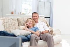 Minnaars die op TV in de woonkamer letten Stock Afbeeldingen