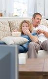 Minnaars die op TV in de woonkamer letten Royalty-vrije Stock Foto's