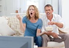 Minnaars die op TV in de woonkamer letten Royalty-vrije Stock Afbeeldingen