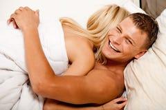 Minnaars gelukkig in bed dat elkaar koestert Royalty-vrije Stock Fotografie