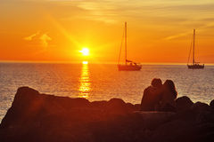 Minnaars op de kade dichtbij overzees bij zonsondergang stock foto's