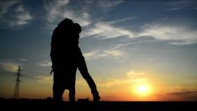 Minnaars op een datum in zonsondergang, het koesteren en het kussen Romantische liefdescène, stock footage