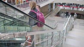 Minnaars op roltrap in luchthaven stock videobeelden