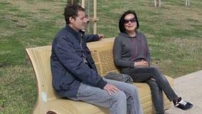 Minnaarsman en vrouw die terwijl het zitten op een parkbank spreken stock video