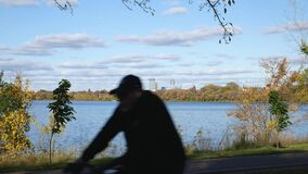 Minneapolis, Minnesota skyline over Lake Calhoun or Lake Bde Maka Ska with autumn foliage, blue sky, fluffy clouds and the blurred. MINNEAPOLIS, MN - 24 OCT 2019 stock video footage