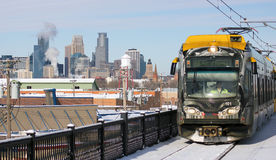 Minneapolis skyline with light rail train. A light rail tran passes by the Minneapolis city skyline in Winter royalty free stock photos