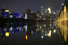 Minneapolis skyline at night. Minneapolis at night reflected in the river with the Stone Arch Bridge royalty free stock photos