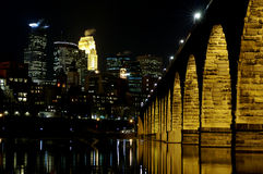 Minneapolis skyline at night. Minneapolis at night reflected in the river with the Stone Arch Bridge royalty free stock photo